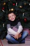 Χαμογελώντας μικρό παιδί με το παρόν κιβώτιο κάτω από το χριστουγεννιάτικο δέντρο στοκ εικόνα με δικαίωμα ελεύθερης χρήσης