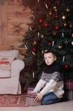 Χαμογελώντας μικρό παιδί με το παρόν κιβώτιο κάτω από το χριστουγεννιάτικο δέντρο στοκ εικόνες