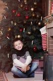 Χαμογελώντας μικρό παιδί με το παρόν κιβώτιο κάτω από το χριστουγεννιάτικο δέντρο στοκ φωτογραφίες