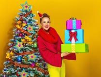 Χαμογελώντας μοντέρνη γυναίκα με το σωρό των κιβωτίων χριστουγεννιάτικου δώρου Στοκ εικόνα με δικαίωμα ελεύθερης χρήσης