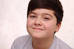χαμογελώντας μυστήριο αγόρι σε ένα άσπρο υπόβαθρο στοκ εικόνα με δικαίωμα ελεύθερης χρήσης