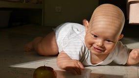 Χαμογελώντας μωρό που προσπαθεί να πιάσει ένα μήλο στο πάτωμα απόθεμα βίντεο