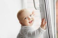 Χαμογελώντας μωρό που στέκεται κοντά στο ανοικτό παράθυρο, λίγο μικρό παιδί Στοκ εικόνα με δικαίωμα ελεύθερης χρήσης