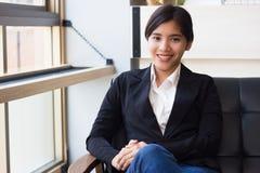 Χαμογελώντας νέα ασιατική επιχειρησιακή γυναίκα που φαίνεται βέβαια και ευτυχής Στοκ Φωτογραφία