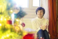 Χαμογελώντας νέα γυναίκα με το φλυτζάνι της καυτής σοκολάτας μπροστά από τα φω'τα Χριστουγέννων στοκ φωτογραφίες