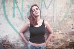 Χαμογελώντας νέα γυναίκα μπροστά από μια καρδιά γκράφιτι στοκ φωτογραφίες