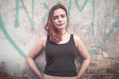 Χαμογελώντας νέα γυναίκα μπροστά από μια καρδιά γκράφιτι στοκ εικόνα