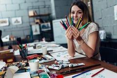 Χαμογελώντας νέα γυναίκα που κρατά μια δέσμη των κραγιονιών που κάθονται στο γραφείο που περιβάλλεται από τις προμήθειες τέχνης Στοκ Φωτογραφία