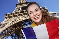 Χαμογελώντας νέα γυναίκα που παρουσιάζει σημαία στο Παρίσι, Γαλλία Στοκ Φωτογραφίες