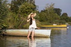 Χαμογελώντας νέα γυναίκα που στέκεται σε μια βάρκα το καλοκαίρι στοκ εικόνες με δικαίωμα ελεύθερης χρήσης