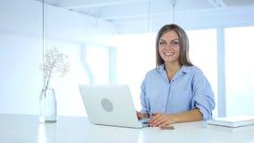 Χαμογελώντας νέα γυναίκα στην εργασία που κοιτάζει προς τη κάμερα απόθεμα βίντεο