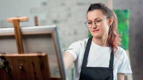 Χαμογελώντας νέα γυναίκα στην ποδιά που απολαμβάνει την εικόνα σχεδίων στη μέση κινηματογράφηση σε πρώτο πλάνο στούντιο τέχνης απόθεμα βίντεο