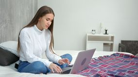Χαμογελώντας νέα γυναίκα freelancer που εργάζεται χρησιμοποιώντας τη συνεδρίαση lap-top στο κρεβάτι στο άνετο σπίτι απόθεμα βίντεο