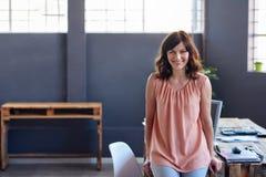 Χαμογελώντας νέα επιχειρηματίας που κλίνει σε ένα γραφείο σε ένα γραφείο Στοκ φωτογραφία με δικαίωμα ελεύθερης χρήσης