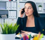 Χαμογελώντας νέα επιχειρηματίας που μιλά στο τηλέφωνο στην αρχή Στοκ φωτογραφίες με δικαίωμα ελεύθερης χρήσης