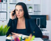 Χαμογελώντας νέα επιχειρηματίας που μιλά στο τηλέφωνο στην αρχή Στοκ φωτογραφία με δικαίωμα ελεύθερης χρήσης