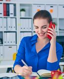 Χαμογελώντας νέα καυκάσια επιχειρηματίας που μιλά στο τηλέφωνο στην αρχή και την παραγωγή των σημειώσεων στο σημειωματάριο Στοκ εικόνα με δικαίωμα ελεύθερης χρήσης