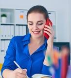 Χαμογελώντας νέα καυκάσια επιχειρηματίας που μιλά στο τηλέφωνο στην αρχή και την παραγωγή των σημειώσεων στο σημειωματάριο Στοκ Φωτογραφίες