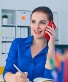 Χαμογελώντας νέα καυκάσια επιχειρηματίας που μιλά στο τηλέφωνο στην αρχή και την παραγωγή των σημειώσεων στο σημειωματάριο Στοκ Φωτογραφία