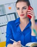 Χαμογελώντας νέα καυκάσια επιχειρηματίας που μιλά στο τηλέφωνο στην αρχή και την παραγωγή των σημειώσεων στο σημειωματάριο Στοκ εικόνες με δικαίωμα ελεύθερης χρήσης