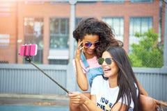 Χαμογελώντας νέες φίλες που γελούν και που παίρνουν selfies μαζί το ο στοκ φωτογραφία με δικαίωμα ελεύθερης χρήσης