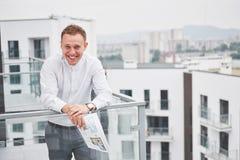 Χαμογελώντας νέος αρχιτέκτονας ή οικοδόμος εφαρμοσμένης μηχανικής στο σκληρό καπέλο με την ταμπλέτα πέρα από την ομάδα οικοδόμων  Στοκ Εικόνα