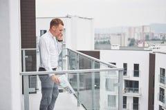 Χαμογελώντας νέος αρχιτέκτονας ή οικοδόμος εφαρμοσμένης μηχανικής στο σκληρό καπέλο με την ταμπλέτα πέρα από την ομάδα οικοδόμων  Στοκ Φωτογραφίες