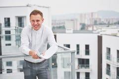 Χαμογελώντας νέος αρχιτέκτονας ή οικοδόμος εφαρμοσμένης μηχανικής στο σκληρό καπέλο με την ταμπλέτα πέρα από την ομάδα οικοδόμων  Στοκ Εικόνες
