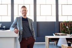 Χαμογελώντας νέος επιχειρηματίας που στέκεται μόνο σε ένα σύγχρονο γραφείο Στοκ εικόνα με δικαίωμα ελεύθερης χρήσης