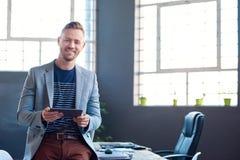 Χαμογελώντας νέος επιχειρηματίας που χρησιμοποιεί μια ταμπλέτα σε ένα γραφείο Στοκ Εικόνες