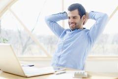 Χαμογελώντας νέος επιχειρηματίας στο γραφείο γραφείων Στοκ Φωτογραφίες