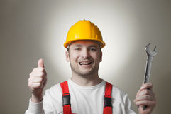 Χαμογελώντας νέος εργαζόμενος με ένα γαλλικό κλειδί Στοκ εικόνα με δικαίωμα ελεύθερης χρήσης