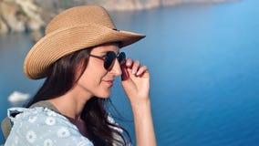 Χαμογελώντας νέος τουρίστας γυναικών που χαλαρώνει έχοντας τη θετική συγκίνηση στο μπλε σαφές υπόβαθρο θάλασσας απόθεμα βίντεο