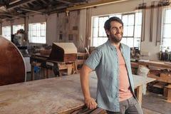 Χαμογελώντας νέος woodworker που κλίνει σε έναν πίνακα στο εργαστήριό του Στοκ φωτογραφίες με δικαίωμα ελεύθερης χρήσης