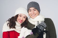 Χαμογελώντας νέο ασιατικό ζεύγος που φορά το πλεκτό θερμό μαντίλι, πέρα από γκρίζο Στοκ φωτογραφία με δικαίωμα ελεύθερης χρήσης