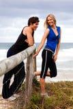 Χαμογελώντας νέο ζεύγος από τη φραγή στην παραλία στοκ εικόνες