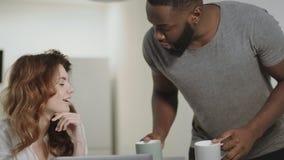 Χαμογελώντας νέο ζεύγος που μιλά στην κουζίνα πρωινού Εύθυμος καφές οικογενειακής κατανάλωσης απόθεμα βίντεο
