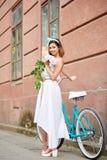 Χαμογελώντας νέο θηλυκό στην άσπρη τοποθέτηση φορεμάτων με τα peonies κοντά στο μπλε ποδήλατο μπροστά από το κόκκινο ιστορικό κτή στοκ φωτογραφίες