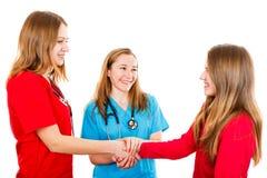Χαμογελώντας νέο κορίτσι και pediatricians στοκ εικόνα