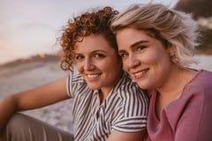 Χαμογελώντας νέο λεσβιακό ζεύγος που απολαμβάνει ένα ρομαντικό ηλιοβασίλεμα παραλιών από κοινού στοκ φωτογραφίες με δικαίωμα ελεύθερης χρήσης