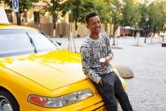 Χαμογελώντας νεαρός άνδρας με τον καφέ φλυτζανιών ο υπό εξέταση και onever στην τσέπη, που κάθεται στην κουκούλα στοκ φωτογραφία