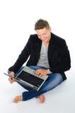 Χαμογελώντας νεαρός άνδρας στο lap-top Στοκ Εικόνες