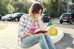 Χαμογελώντας νερό και ανάγνωση γυναικών πόσιμο ενός βιβλίου ανασκόπηση αστική Στοκ εικόνα με δικαίωμα ελεύθερης χρήσης