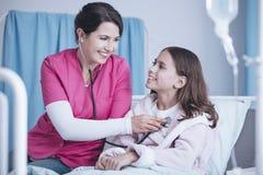 Χαμογελώντας νοσοκόμα με το στηθοσκόπιο που εξετάζει το ευτυχές κορίτσι στο hospi στοκ φωτογραφία με δικαίωμα ελεύθερης χρήσης