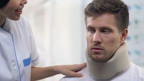 Χαμογελώντας νοσοκόμα που εφαρμόζει το αρσενικό υπομονετικό αυχενικό περιλαίμιο αφρού, τραυματισμοί λαιμών απόθεμα βίντεο