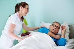 Χαμογελώντας νοσοκόμα της Νίκαιας που εξετάζει υπομονετική ποιους που κοιμούνται και που ονειρεύονται Στοκ φωτογραφία με δικαίωμα ελεύθερης χρήσης