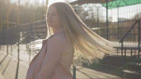 Χαμογελώντας ξανθή γυναίκα που εξετάζει τη κάμερα υπαίθρια στο ηλιοβασίλεμα σε σε αργή κίνηση απόθεμα βίντεο