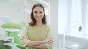 Χαμογελώντας οδοντίατρος στο οδοντικό εσωτερικό κλινικών Πορτρέτο του οδοντιάτρου γυναικών φιλμ μικρού μήκους