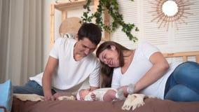 Χαμογελώντας οικογένεια στο κρεβάτι όπου ο μπαμπάς και mom προσέχει, αγγίζει και μιλά με την κόρη μωρών τους απόθεμα βίντεο