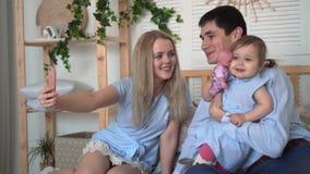 Χαμογελώντας οικογένεια στο κρεβάτι, όπου ο μπαμπάς και mom το παιχνίδι με τη μικρή κόρη τους, mom παίρνουν ένα selfie της οικογέ φιλμ μικρού μήκους